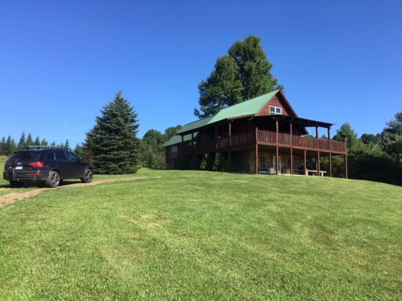 A rental cabin with lush green lawn in front and evergreen trees behind it.